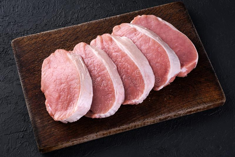 Raw sliced pork loin on a dark background. Fresh meat. stock image