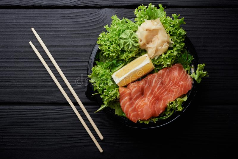 Raw Sliced Salmon Fillet on Black Stone Background. Thick Pieces of Fresh Trout. Red Fish Sashimi. With wasabi and ginger royalty free stock images