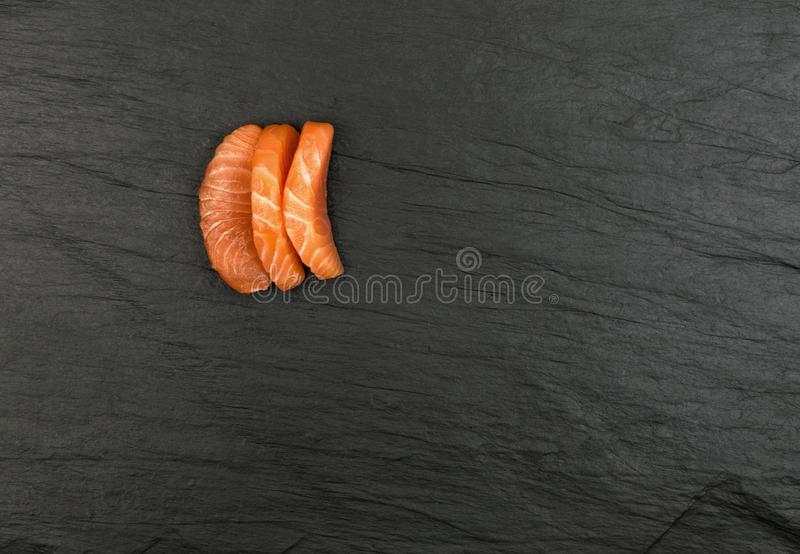 Smoked Salmon Fillet. Raw Sliced Salmon Fillet on Black Stone Background. Thick Pieces of Fresh Trout. Red Fish Sashimi royalty free stock photos