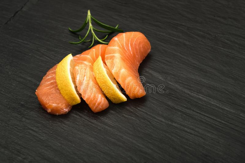 Smoked Salmon Fillet. Raw Sliced Salmon Fillet on Black Stone Background. Thick Pieces of Fresh Trout. Red Fish Sashimi royalty free stock photo