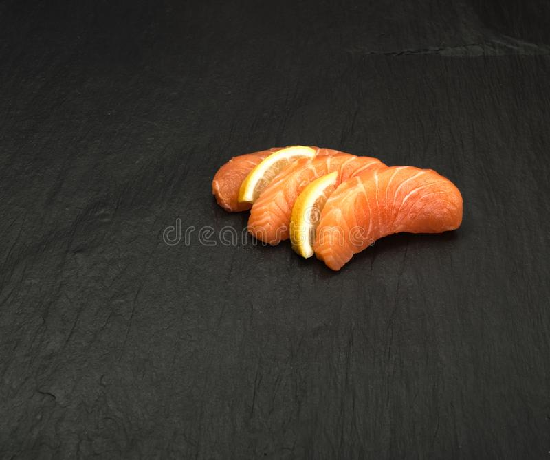 Smoked Salmon Fillet. Raw Sliced Salmon Fillet on Black Stone Background. Thick Pieces of Fresh Trout. Red Fish Sashimi stock photos