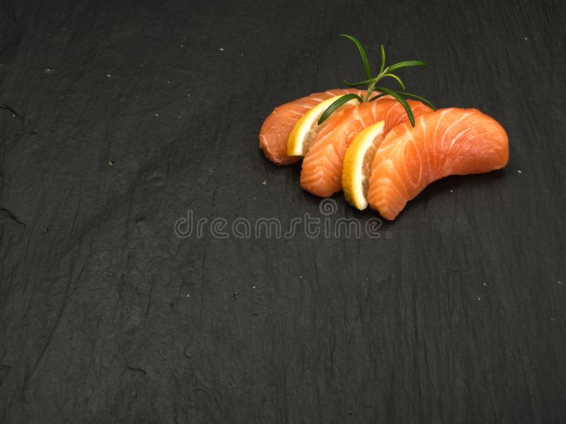 Smoked Salmon Fillet. Raw Sliced Salmon Fillet on Black Stone Background. Thick Pieces of Fresh Trout. Red Fish Sashimi royalty free stock photography