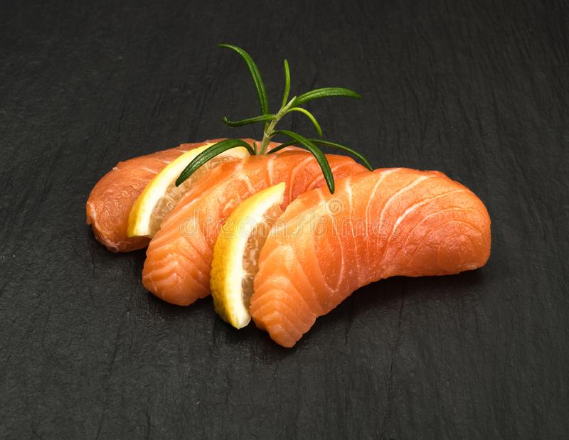 Smoked Salmon Fillet. Raw Sliced Salmon Fillet on Black Stone Background. Thick Pieces of Fresh Trout. Red Fish Sashimi royalty free stock images