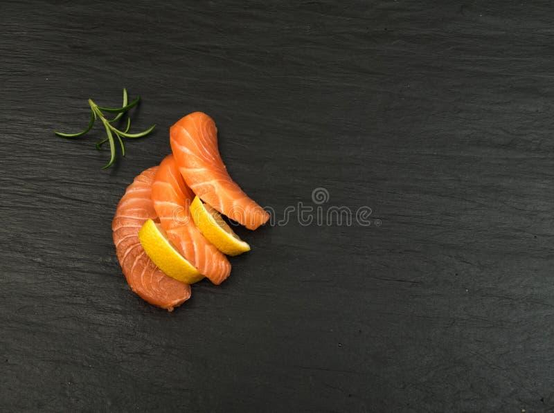 Smoked Salmon Fillet. Raw Sliced Salmon Fillet on Black Stone Background. Thick Pieces of Fresh Trout. Red Fish Sashimi stock photos