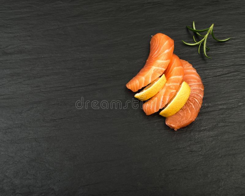 Smoked Salmon Fillet. Raw Sliced Salmon Fillet on Black Stone Background. Thick Pieces of Fresh Trout. Red Fish Sashimi stock images