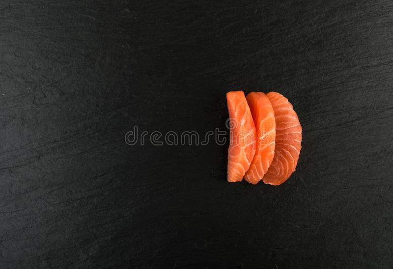 Smoked Salmon Fillet. Raw Sliced Salmon Fillet on Black Stone Background. Thick Pieces of Fresh Trout. Red Fish Sashimi stock photography