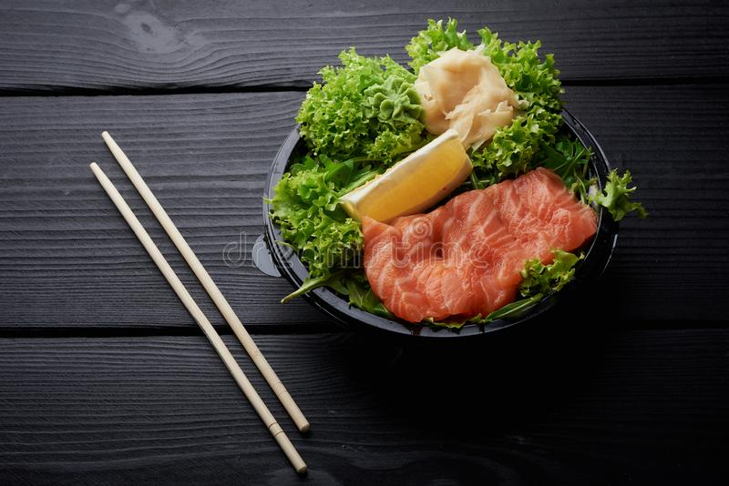 Raw Sliced Salmon Fillet on Black Stone Background. Thick Pieces of Fresh Trout. Red Fish Sashimi stock photos