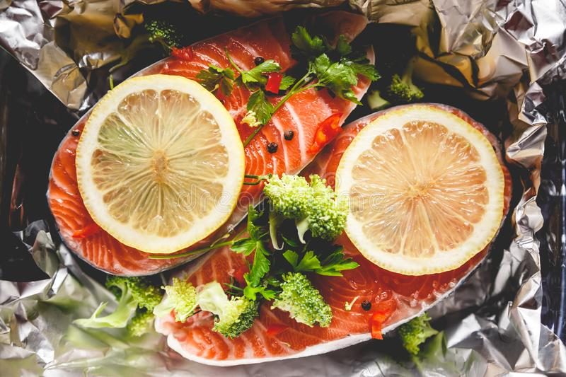 Raw sockeye salmon steaks on foil before baking in oven. Raw sockeye salmon steaks on foil before baking in oven royalty free stock image