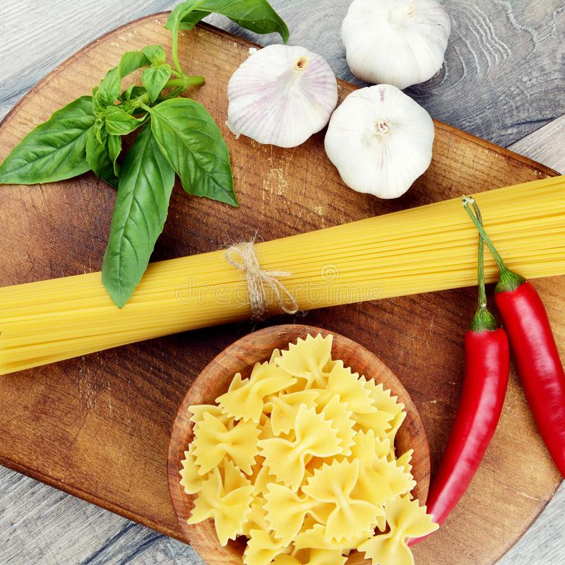 Raw spagetti and farfalle pasta on the table. Raw spagetti and farfalle pasta on the wooden table stock image