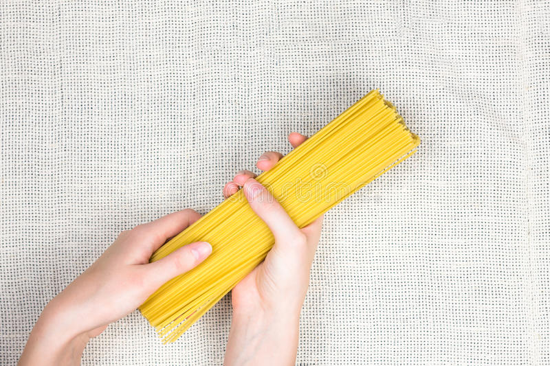 Raw spaghetti in female hands flat lay stock images