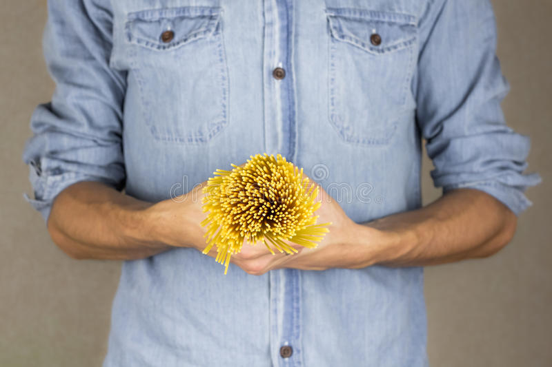 Raw spaghetti in male hands royalty free stock photography