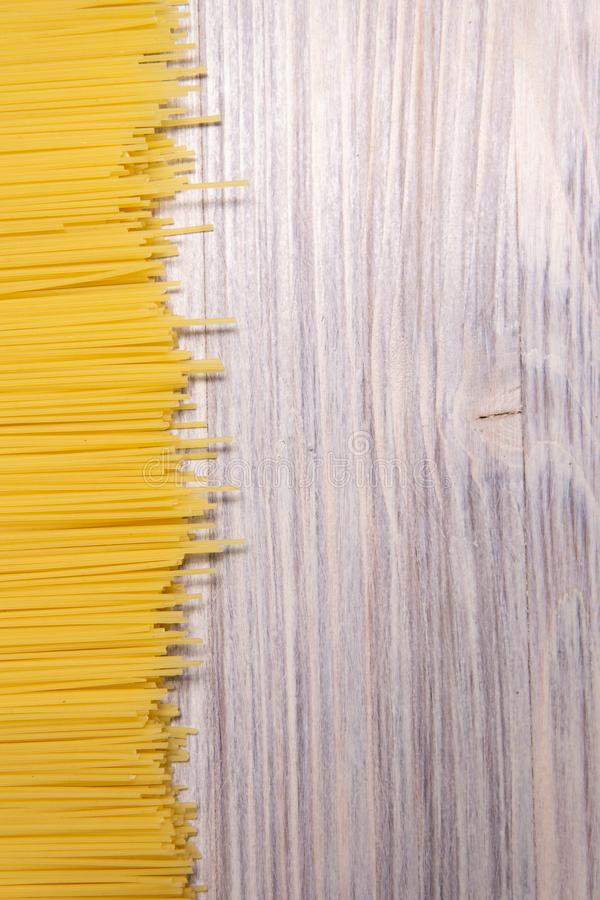 raw spaghetti pasta scattered on wooden table, close-up view from above stock images