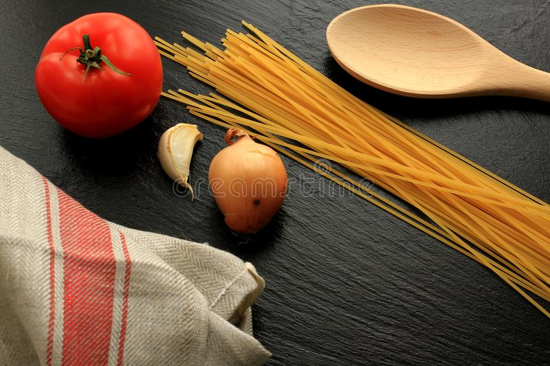 Raw spaghetti with tomato, garlic, onion, wooden trowel and kitchen towel royalty free stock photography