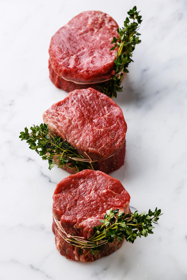 Raw Steak filet mignon. Raw fresh marbled meat Steak filet mignon and thyme on white marble background stock photos