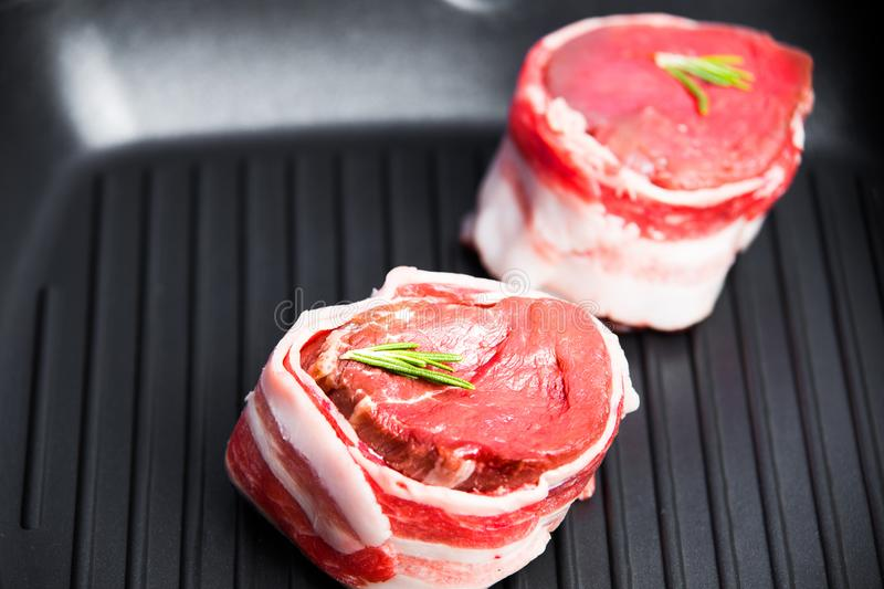 Raw fresh steak. Raw steak fillet mignon in a grilled pan close-up with a sprig of rosemary. Theme of tasty and healthy food stock photo