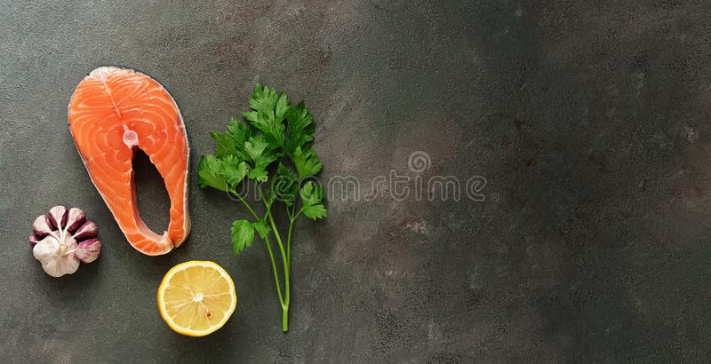 Raw steak fish salmon, lemon,parsley and garlic on a dark rustic background, banner. Top view, flat lay, copy space.  royalty free stock photo
