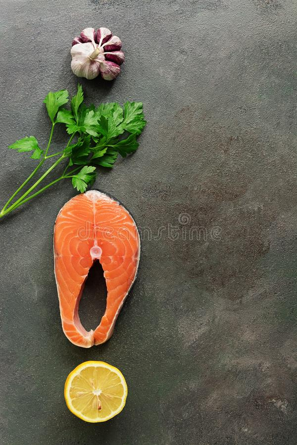 Raw steak fish salmon, lemon,parsley and garlic on a dark rustic background, vertical border. Top view, flat lay, copy space royalty free stock image