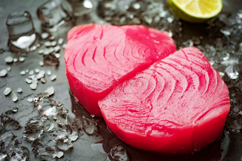 Raw steak of tuna yellowfin fillets. Sliced fillets of tuna on a stone background with salt and ice cook cooking dinner filet fish food fresh healthy ingredient stock image
