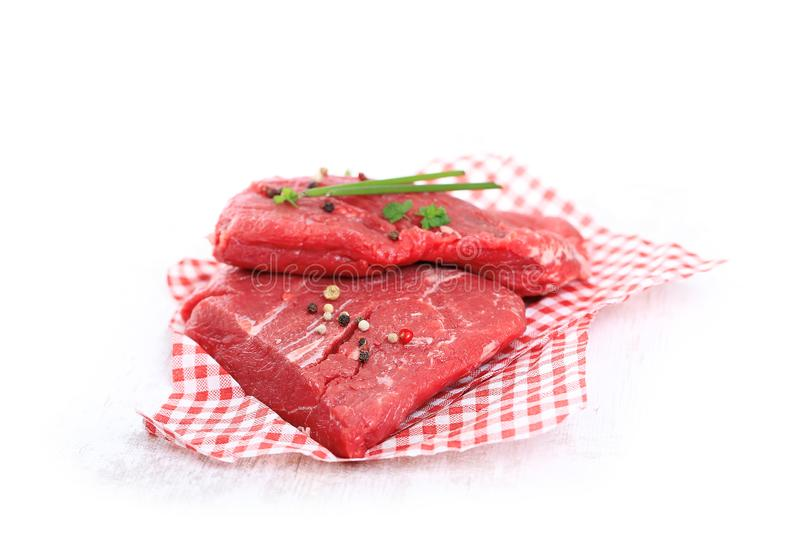 Raw steak on wooden  background. Raw steak on white wooden background, meat spices and parsley royalty free stock photography