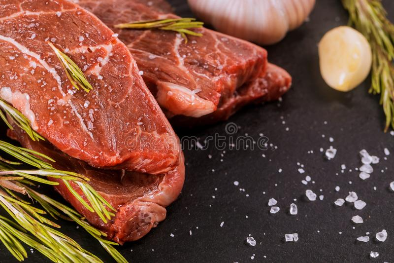 Raw striploin steak with rosemary and garlic, salt and pepper over stone table royalty free stock photo