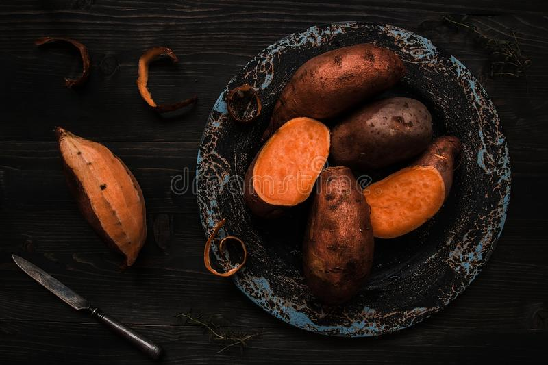 Raw sweet potato on the wooden black table top view royalty free stock photography