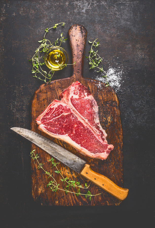 Raw T-bone Steak for grill or BBQ with fresh herbs and oil and kitchen knife on dark aged cutting board. And rust metal background, top view royalty free stock images