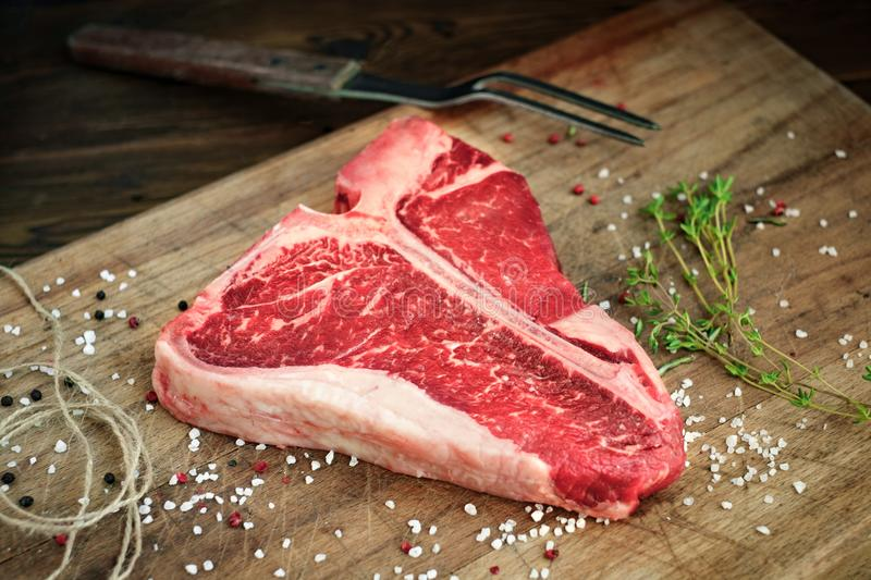 Raw t bone steak on wooden Board rustic style royalty free stock images