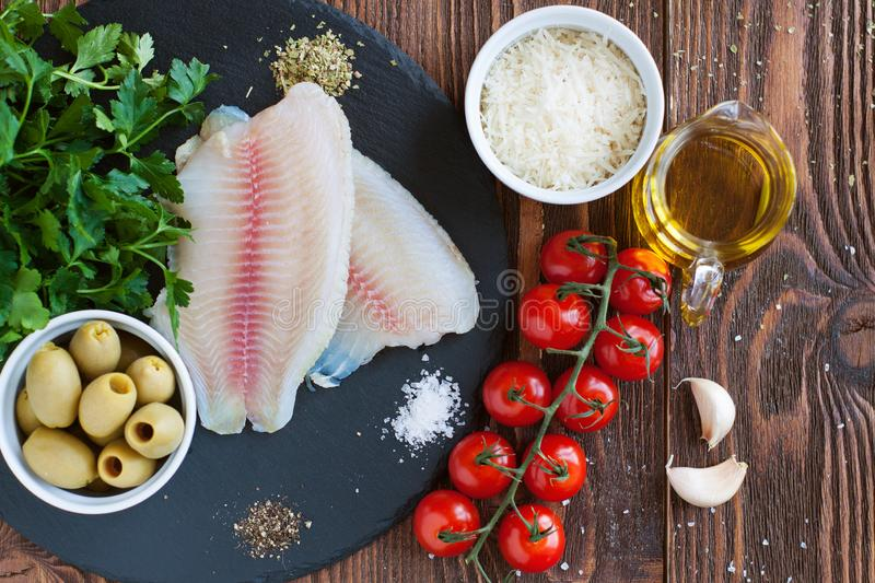 Raw tilapia and vegetables, ingredients for mediterranean style baked fish stock photos