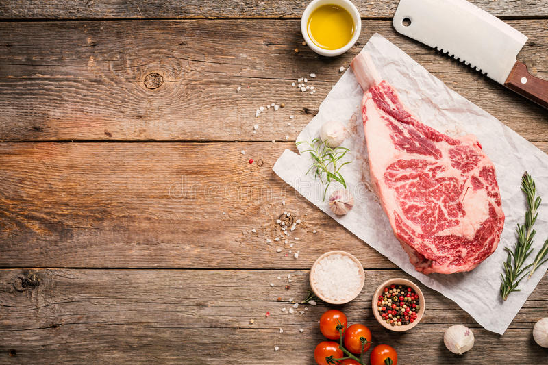 Raw tomahawk beef steak. With ingredients for grilling: seasoning, fresh rosemary and olive oil on wooden background, top view royalty free stock photography