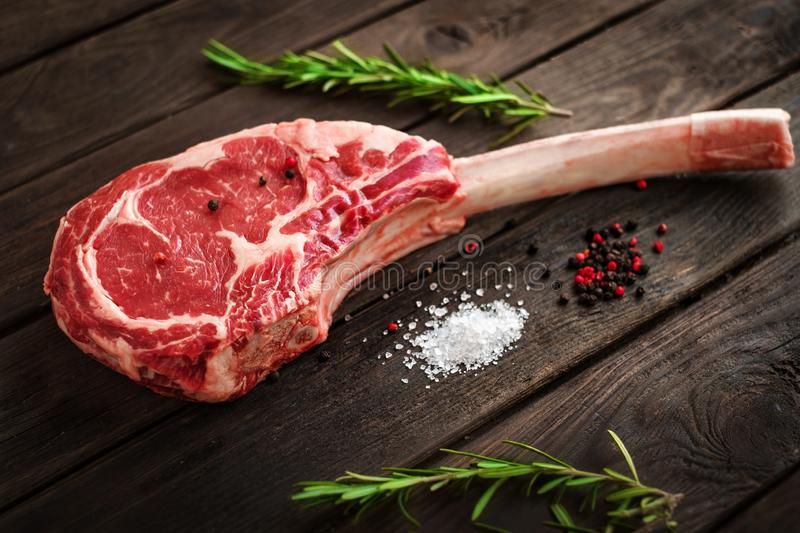 Raw Tomahawk steak on wooden background with spices for grilling. Rustic style royalty free stock photo