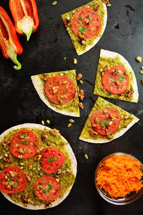 Raw Tortilla Pizza with Pesto, Nuts, Seeds and Tomatoes royalty free stock image