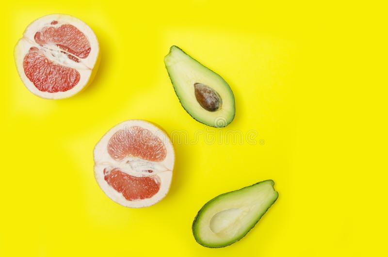 Sliced grapefruit and avocado on bright yellow backgroun, top view. Raw tropical fruits on yellow background, top view.Concept of sweet summer time Sliced royalty free stock photos