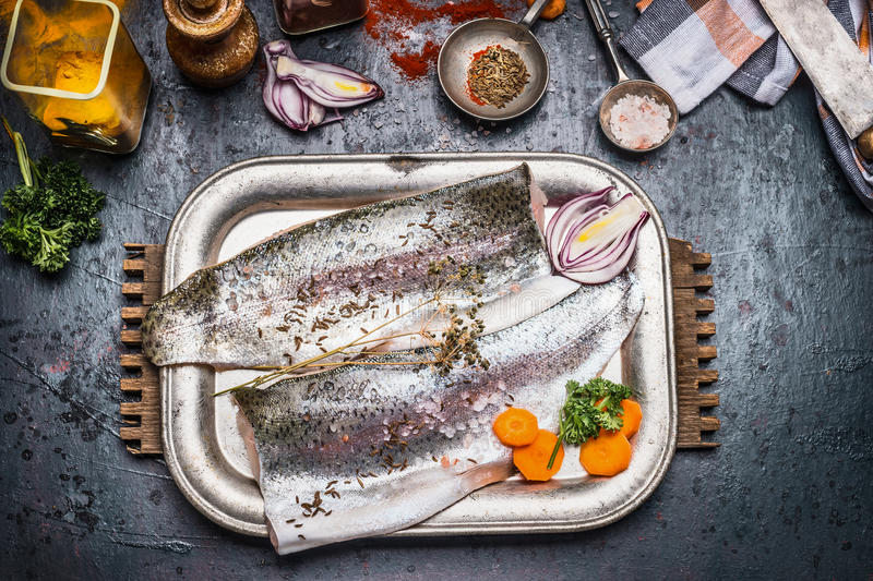 Raw trout fish fillet preparation with gut vegetables, fennel seeds, salt and seasoning for tasty cooking on dark rustic backgrou stock photo