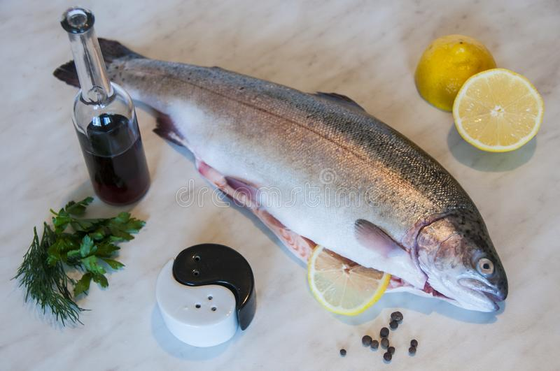 Raw trout with red vine, slices of lemon, bunch of greens, pepper and salt on a marble background. Fresh fish dish. royalty free stock photos
