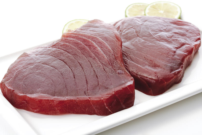 Raw tuna filet steaks on plate with lime royalty free stock photography