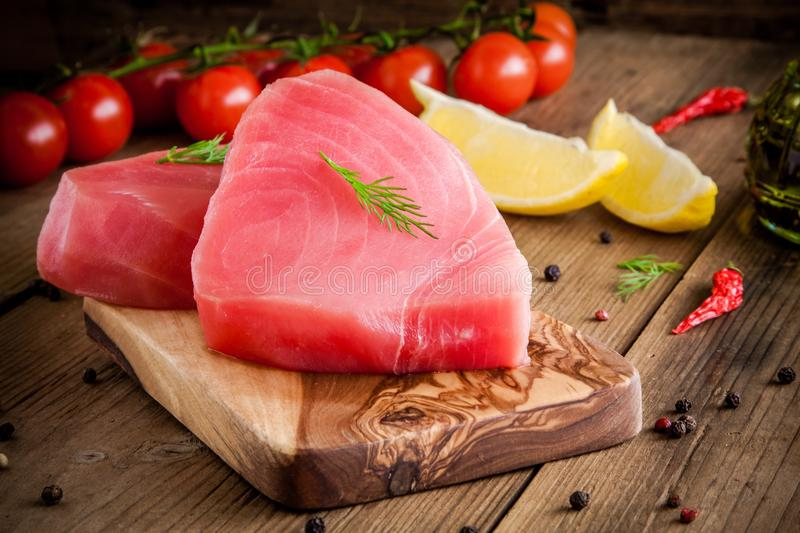 Raw tuna fillet with dill, lemon and cherry tomatoes. In olive cutting board royalty free stock image