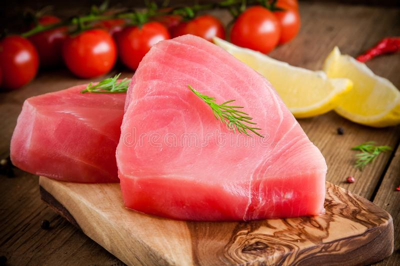 Raw tuna fillet with dill, lemon and cherry tomatoes. In olive cutting board royalty free stock images