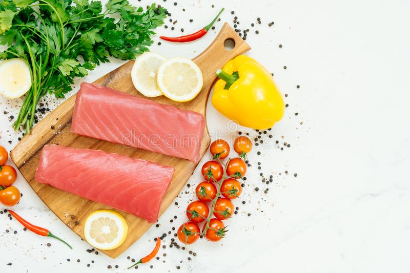 Raw tuna fish fillet meat. On wooden cutting board with vegetable and ingredient for cooking royalty free stock photo