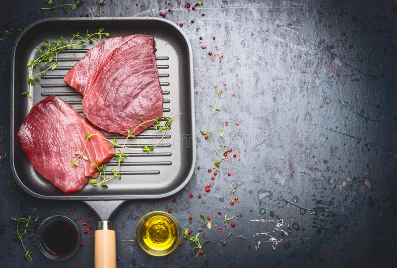 Raw Tuna Steak in grill frying pan with herbs and oil on dark aged vintage background, top view stock photos