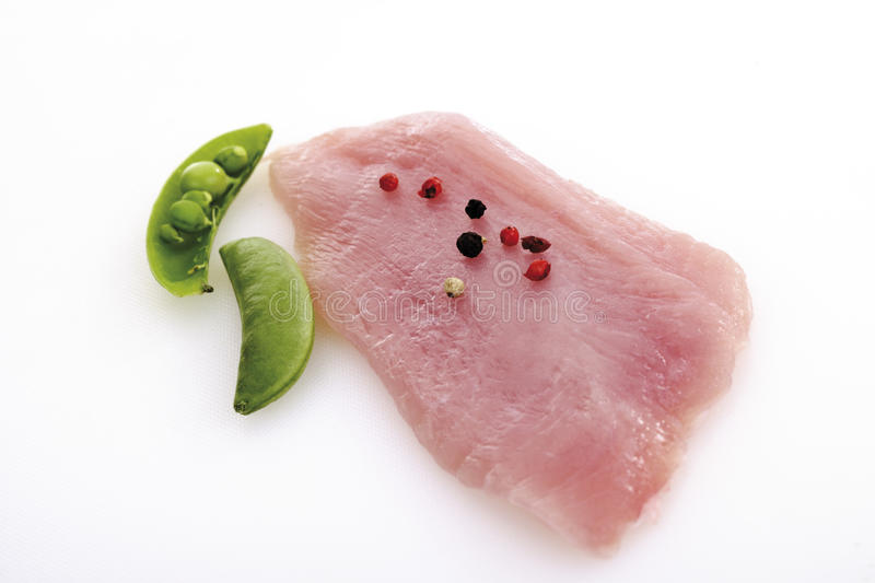 Raw Turkey cutlet, pepper corns and sugar peas stock photography