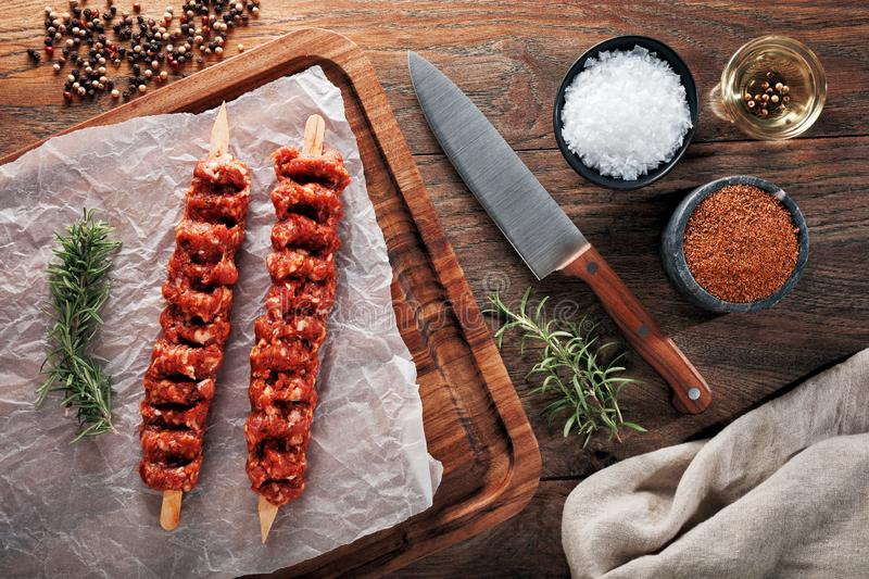 Raw Turkish Adana kebab on white cooking paper and wooden cutting table. Dercorated with herbs, spices and chef`s knife. Raw Turkish Adana kebab on white cooking royalty free stock image