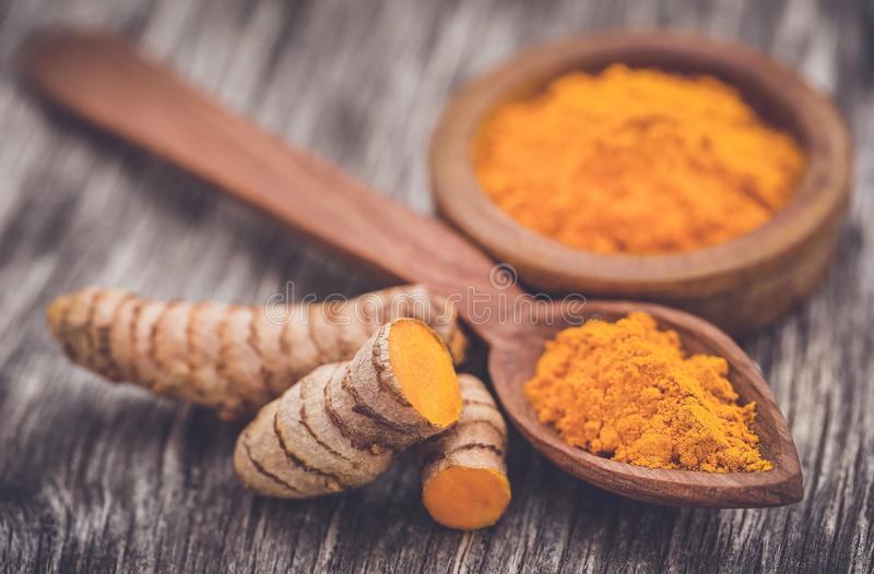 Raw turmeric with powder. In a bow and spoonl on wooden surface royalty free stock image