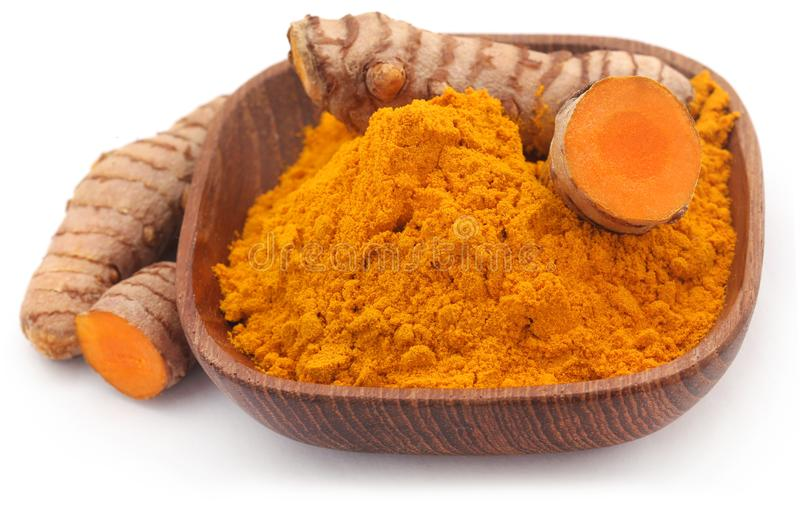 Raw turmeric with powder in a bowl. Over white background stock photography