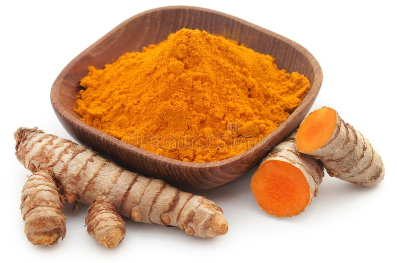 Raw turmeric with powder in a bowl. Over white background royalty free stock photo