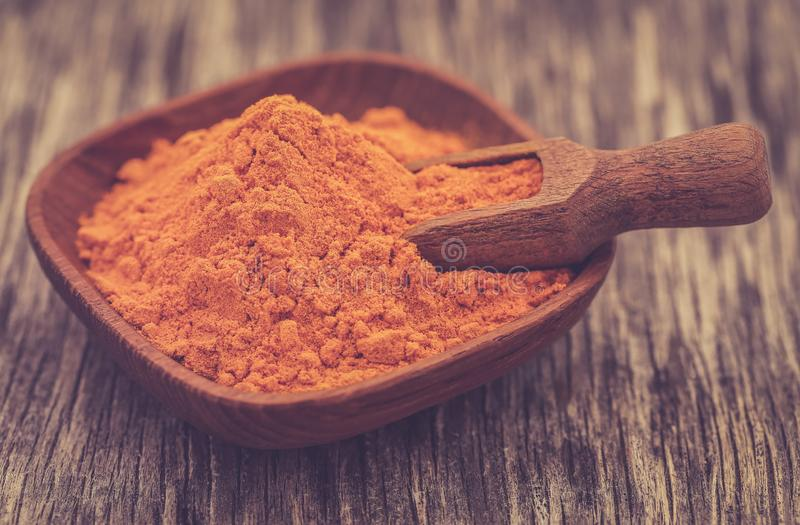 Raw turmeric with powder. In a bowl on wooden surface royalty free stock images