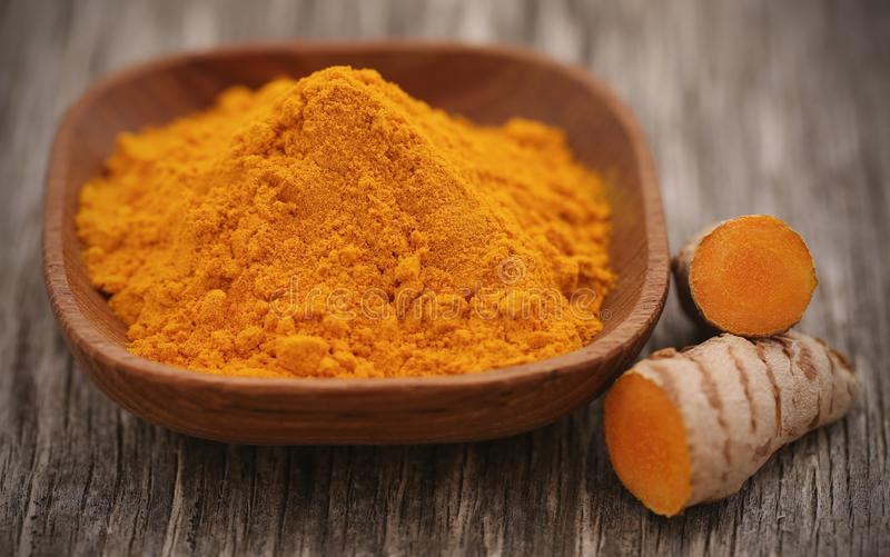 Raw turmeric with powder. In a bowl on wooden surface royalty free stock photography