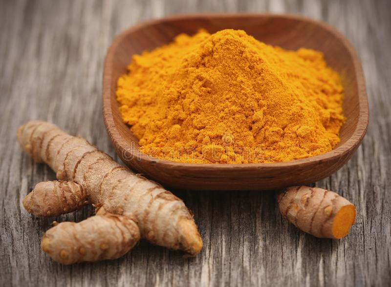 Raw turmeric with powder. In a bowl on wooden surface stock photo