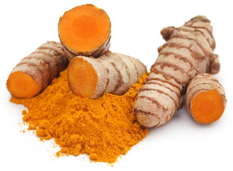 Raw turmeric with powder. Over white background royalty free stock photography