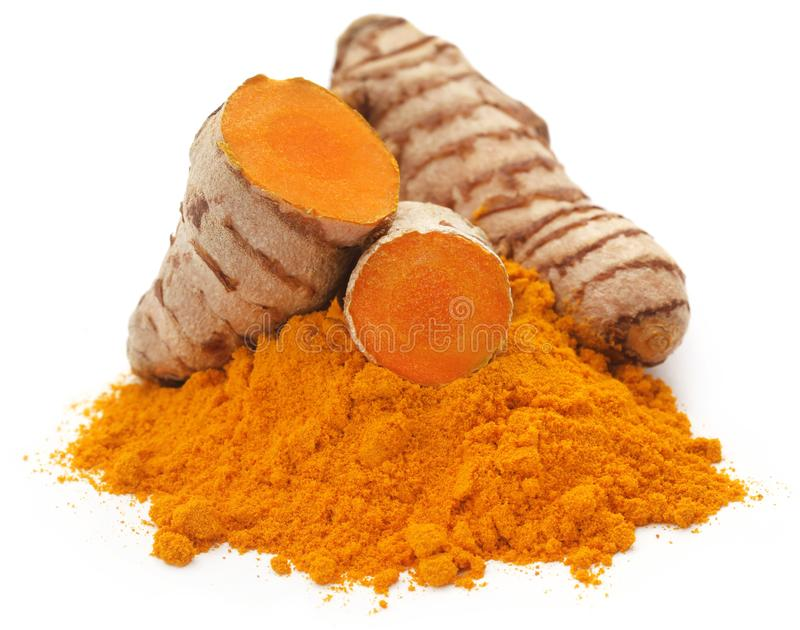 Raw turmeric with powder. Over white background stock photo