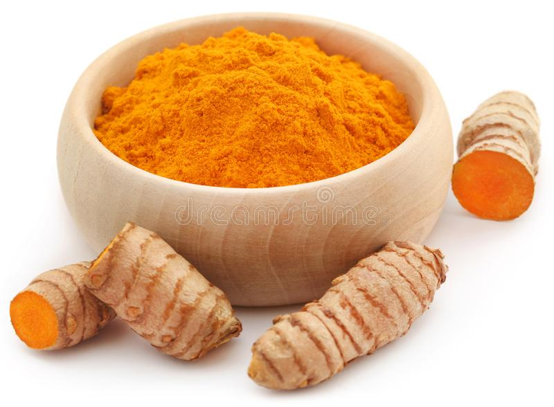 Raw turmeric with powder. In a wooden bowl stock image